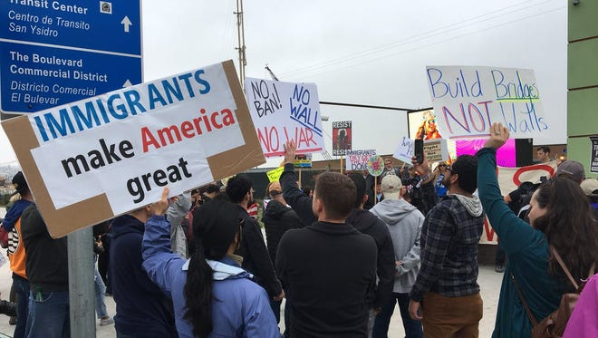 """Protesters hold signs that read """"Immigrants make America great"""" and """"No hate in the Golden State"""" ahead of the President Trump's visit to California on Tuesday, March 13, 2018."""