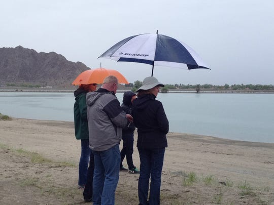 People attending Sunday's Desert Triathlon at Lake Cahuilla in La Quinta carried umbrellas to keep themselves dry as showers passed through the area.