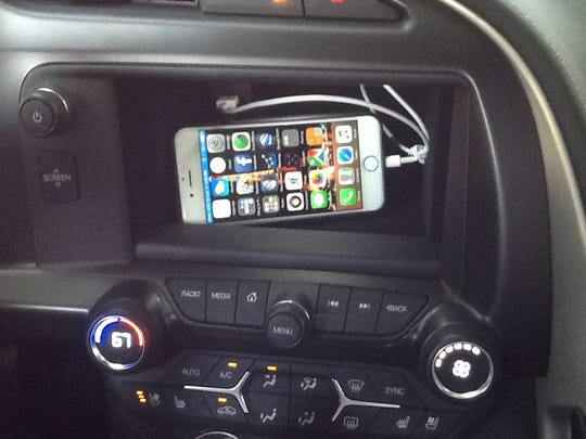 The iPhone must be connected via USB for CarPlay to work. The Corvette's storage bin is barely big enough for large smart phones.