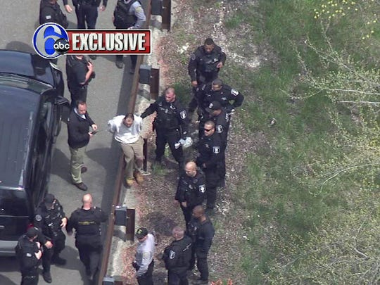 Recaptured fugitive Arthur Buckel is surrounded by NJ Department of Corrections officers after he was apprehended along the Garden State Parkway, just north of the Lacey Rest Area, Monday, May 9, 2016.  IMAGE COURTESY OF WPVI