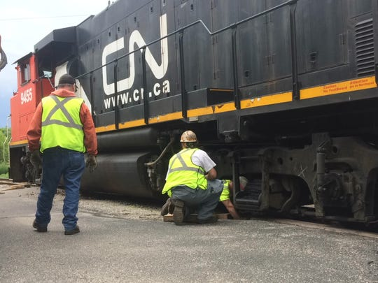 CN employees work on a derailed train engine near Main Avenue in De Pere.