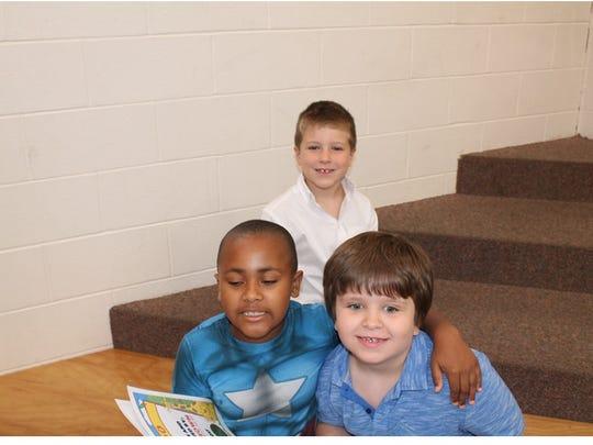 Aidan Brown, Samuel Moore and Ben Howard sharing their books