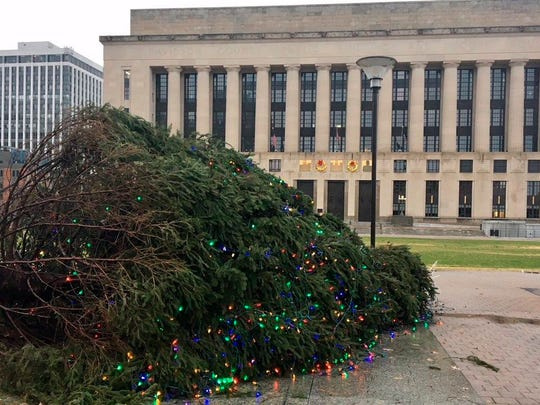 The Christmas tree in Nashville, Tenn.'s Public Square Park lies on its side on Saturday, Dec. 23, 2017. City officials say the culprit was a combination of wind, rain and possibly a defective anchor. A 35-foot tall Christmas tree still stands outside the state Capitol, which is not far from where this tree fell. (Kyle Cooke, Danielle Allen/WSMV via AP)