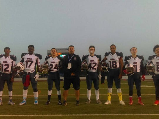 Gulf Coast defensive backs coach P.J. Gibbs (center) poses with Team USA members during the 2016 International Bowl. Gibbs was an assistant coach during the event, which features youth football teams from the United States against teams from other countries. Gibbs is the head coach of the Team USA U17 Stars team this year.