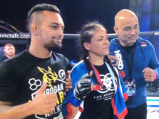 Brogan Walker Sanchez, flanked by husband Mike Sanchez at left, and instructor and coach Stephen Roberto at right, celebrates her win at Invicta FC 27 in Kansas City, MO on Saturday night.