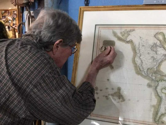 Winston Garth looks over a 17th century map at his