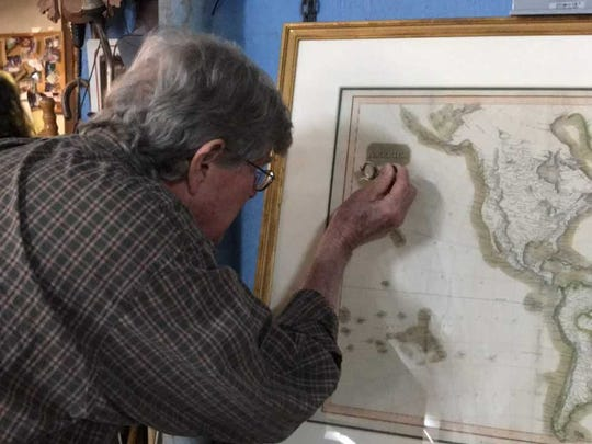 Winston Garth looks over a 17th century map at his shop on Navy Boulevard.
