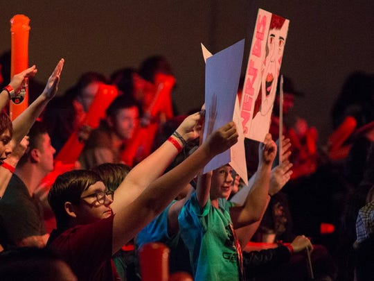 "Fans hold signs to show their support for the teams. The crowd chanted ""Defense!"" and other cheers at the esports competition."