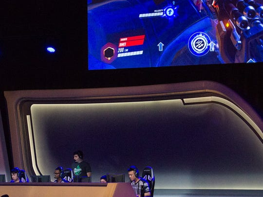 At the 2018 Fiesta Bowl Overwatch Collegiate National Championship, players compete while a large screen reflects the gameplay.