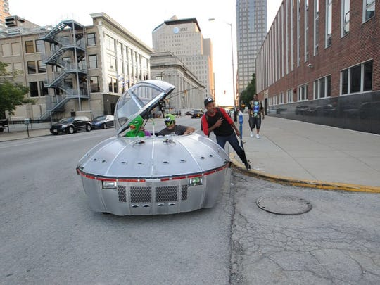Another fan poses alongside Steve Anderson's saucer car built from a cut-down 1991 Geo Metro.