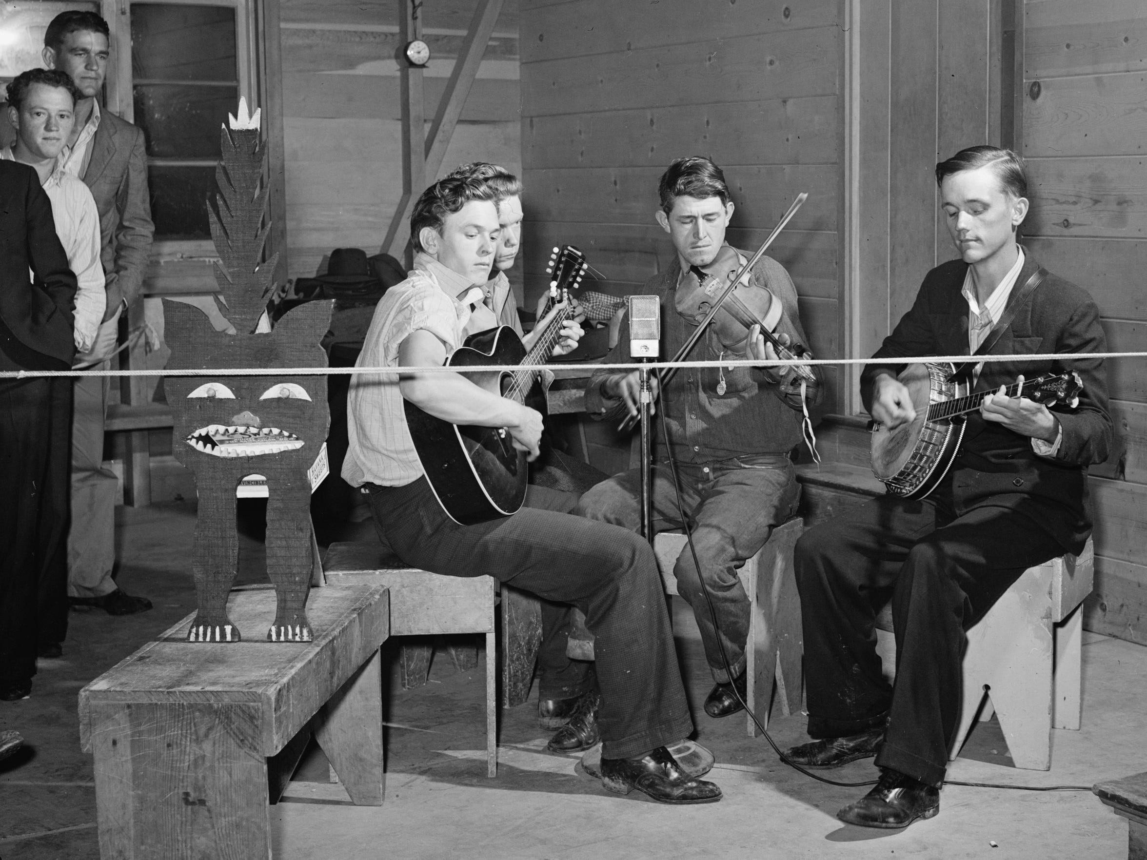 A string band plays at a Saturday night dance at a Tulare migrant camp in March, 1940. The kitty, at left, is ready for contributions. Fiddles, guitars and banjos were common instruments among Dust Bowl migrants to the Central Valley for a simpler country sound than what was popular back in Nashville at the time.