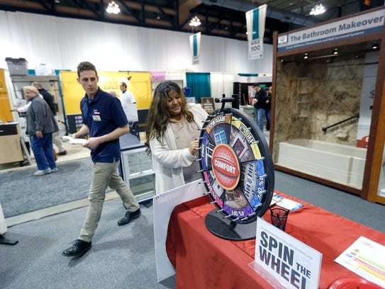 Sonia Tafoya of Rochester spins the Comfort Windows wheel for a prize as home show associate Lucas Hennessey watches during the 2016 Home and Garden Show at the Rochester Riverside Convention Center.