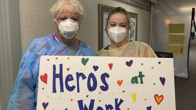 Betsy New, left, and Brooke Hostetler, nursing assistants at Greenville Health and Rehab Center, are lauded in a sign made by Heartland Hospice. The Greenville center has lost several residents to the coronavirus.