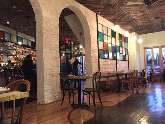 The dining room at Gold Cash Gold in Detroit's Corktown features a stained glass panel that echoes the colorful glass partitions at the front door; the glass work was done by restaurant co-owner Phil Cooley.