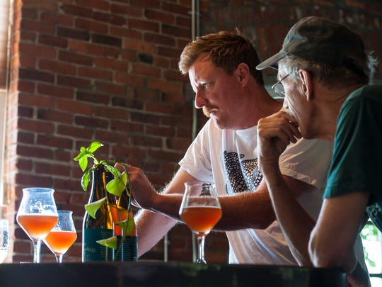 Todd Haire, center, and Bill Mares, collaborators in producing  House of Fermentology sour beers, discuss their beers at Foam Brewery in Burlington on Friday, August 5, 2016.