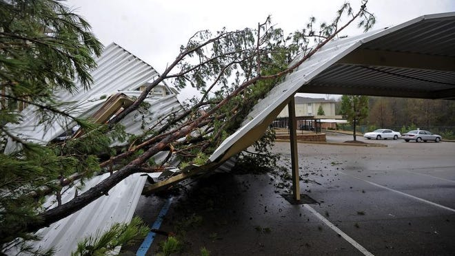 A tree rests on a parking awning at The Connection Apartments in Oxford Friday after storms moved through the area. Much of central and northeast Mississippi was under severe storm warnings or a tornado watch early Friday.