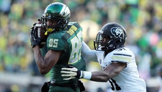 Oregon wide receiver Dwayne Stanford (85) looks for room against Colorado linebacker Kenneth Olugbode (31) on Saturday in Eugene, Ore.