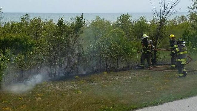 Firefighters quickly extinguished a small brush fire July 16 near Mariners Trail in Two Rivers.