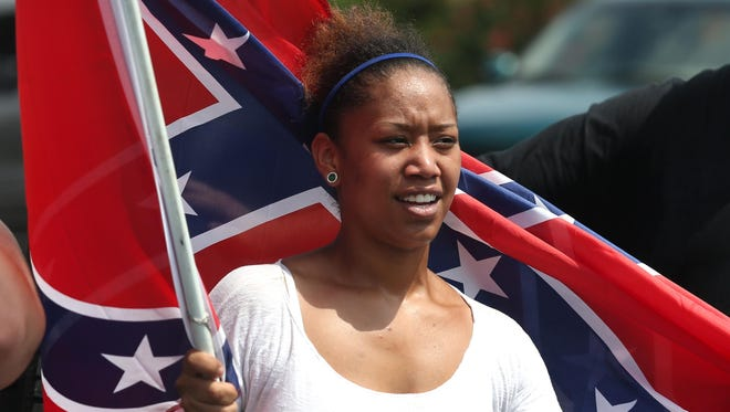 Erika Moreno holds a flag at a pro-Confederate flag rally Sunday in Panama City Beach, Fla.