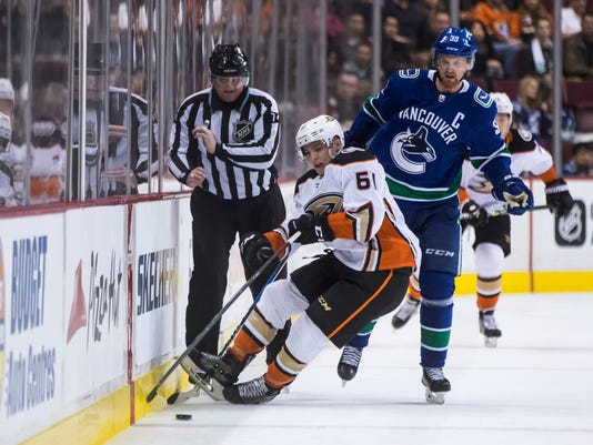 Anaheim Ducks' Troy Terry (61) falls to the ice in front of Vancouver Canucks' Henrik Sedin, of Sweden, and linesman Lonnie Cameron during the first period of an NHL hockey game Tuesday, March, 27, 2018, in Vancouver, British Columbia. (Darryl Dyck/The Canadian Press via AP)
