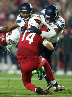 Cardinals quarterback Ryan Lindley is sacked by Seattle Seahawks linebacker O'Brien Schofield during the second quarter at University of Phoenix Stadium on December 21, 2014.