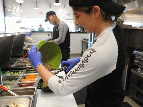 Hailey Wiggins mixes a salad at Body Fuel Bistro, the Port Hueneme restaurant she opened in September with her mother, Angie Wiggins.