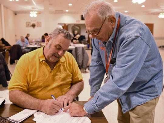 Gregory Smith, left, signs paperwork after Vito Ferraro prepared his taxes Wednesday, Feb. 3, 2016 at Burt J. Asper American Legion Post 46. AARP Tax Aide Program was in session at the facility to help folks prepare their 2015 taxes.