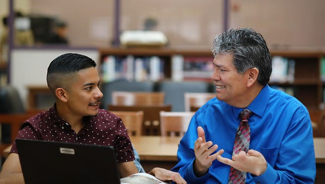 Manuel Mendoza, right, a Spanish teacher at Gadsden High School, talks with former student Gabriel Holguin on a recent day at Gadsden High. Holguin nominated Mendoza for a national recognition, and Mendoza was selected for the award.