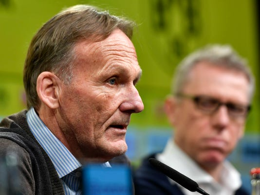 Borussia Dortmund CEO Hans-Joachim Watzke, left, presents Austrian coach Peter Stoeger, right, as the new head coach of the Bundesliga soccer club at a press conference in Dortmund, Germany, Sunday, Dec. 10, 2017. Borussia Dortmund displaced Dutch head coach Peter Bosz yesterday after a defeat against Werder Bremen. Stoeger was dismissed as head coach of FC Cologne earlier this month. (AP Photo/Martin Meissner)