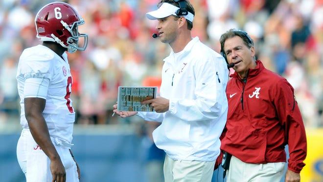 Alabama coach Nick Saban talks to offensive coordinator Lane Kiffin during a 2014 game against Mississippi.