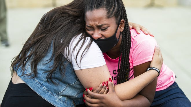 """Natalia Guerrero comforts Carlha Toussaint as she cries in her arms at the DARRC Coalition gathering at Brockton City Hall on Monday, Aug. 31, 2020. """"I want to lament anyone lost from Brockton,"""" said Toussaint, """"They will always be dear to our heart."""" Toussaint's younger brother was friends and grew up with Sgt. Elder Fernandes, who was found hanging in Killeen, Texas, last week."""