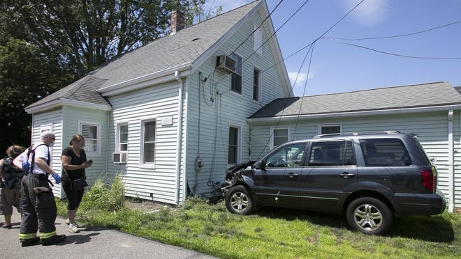 Stoughton Police investigate the scene where a driver crashed a black Honda SUV into a grey Ford pickup truck and then into the home at 156 Pleasant Street on Sunday, July 26, 2020.