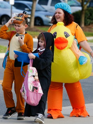 Melissa Tribuiani follows her children, Nico, 10, and Rachel, 7, during Halloween in Hockessin in this News Journal file photo.