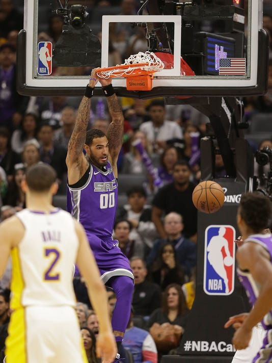 Sacramento Kings center Willie Cauley-Stein, center, hangs from the rim after stuffing dunking against the Los Angeles Lakers during the first quarter of an NBA basketball game Wednesday, Nov. 22, 2017, in Sacramento, Calif. (AP Photo/Rich Pedroncelli)