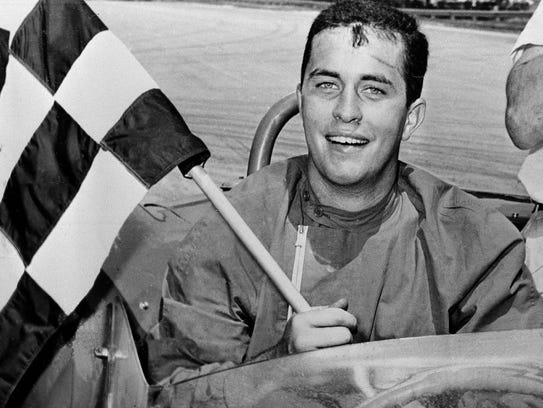 Roger S. Penske displays the checkered flag after he