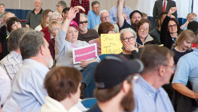 Some attendees of U.S. Rep. Justin Amash's town hall Thursday in Battle Creek held signs, some of which showed support for Planned Parenthood and the Affordable Care Act. Others showed opposition against President Donald Trump.