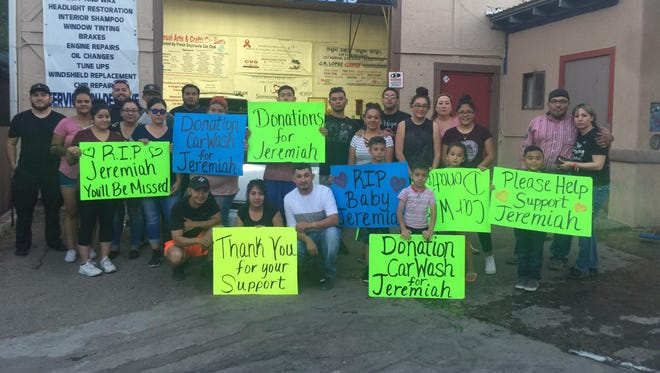 Volunteers hold up signs prior to the car wash fundraiser for Jeremiah.