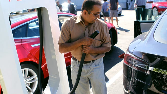 """Ninad Huilgol plugs his Model S into one of Tesla Motors' new """"Supercharger"""" stations at their factory in Fremont, Calif.,"""