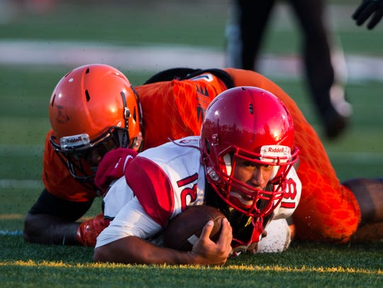 Quarterback R.J. Rosales falls to the ground after being tackled during the spring game against Miami-Carol City in May at Immokalee High School.