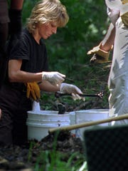 Melissa Butterworth, assistant lab technician with the Hamilton County Sheriff's Department, examines human bones in a wooded area at Fox Hollow Farm in Westfield.
