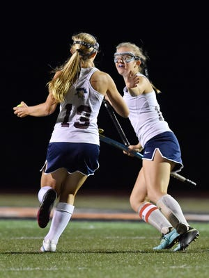 New Oxford's Elizabeth Farmer, left, is greeted by teammate Sara Parrish after scoring the only goal in the second half of the YAIAA field hockey title game Thursday, Oct. 19, 2017, at Northeastern. New Oxford won 1-0 to deliver Bermudian Springs their first season defeat and to win the Colonials' first field hockey championship.