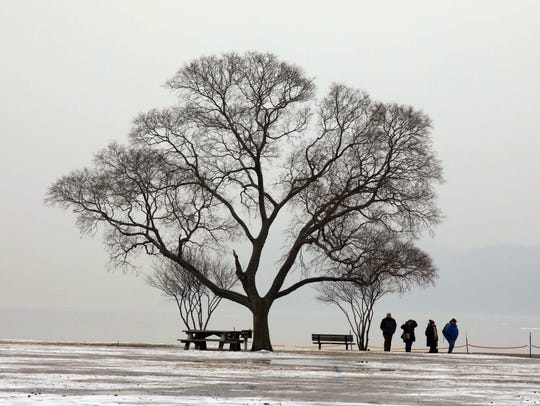 People enjoy a walk by the Hudson River during the