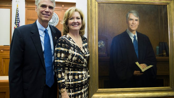 Chief United States District Judge Thomas Varlan and his wife Danni Varlan stand next to his portrait at the Howard H. Baker U.S. Courthouse Friday, April 7, 2017.