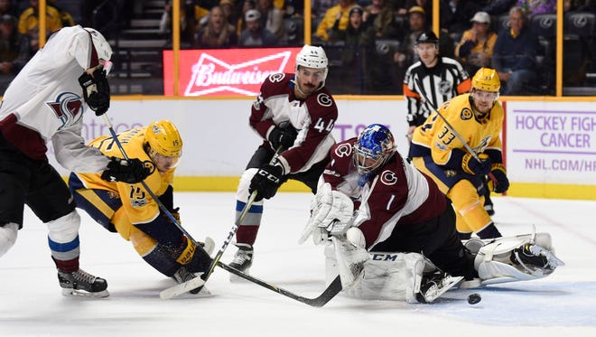 Predators right wing Craig Smith (15) shoots the deflection off Avalanche goalie Semyon Varlamov (1) to score a goal during the first period Saturday.