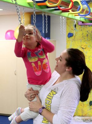 Physical therapist Rebecca Hawkins works with client Addy, 5, at the Children's Center for Growth and Development in Hartland Township. The center will host a free program on child development Monday.