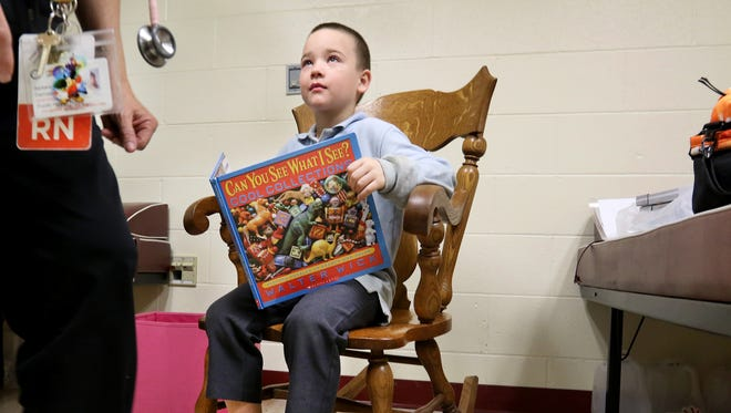 Arthur Murray, 8, talks with nurse Barb Demasi at Ethel M. Taylor Academy. The first-grader needed fresh clothes, head to toe.