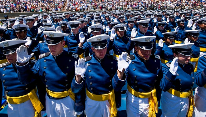 Cadets raise their right hands as they take the oath of office to become 2nd Lieutenants during the graduation ceremony for the United States Air Force Academy class of 2014 at Falcon Stadium in Colorado Springs, Colo., on May 28, 2014.