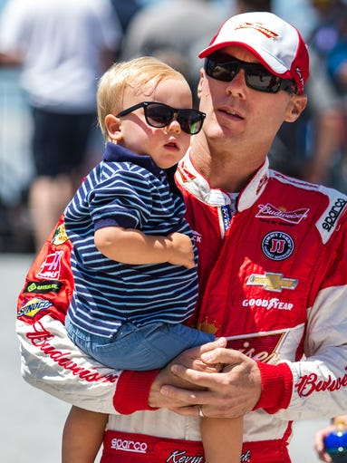 Kevin Harvick carries his son Keelan with him to the driver introductions stage before the start of the FedEx 400 at Dover International Speedway on Sunday morning, June 1, 2014.