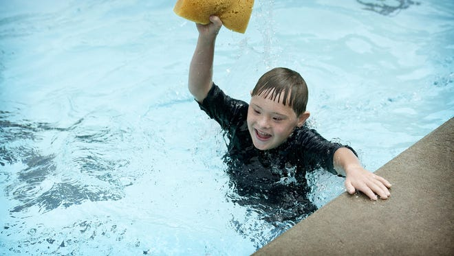 Max Condon, 9, plays with a sponge in the pool at the Jewish Community Center during Camp Tikvah on Aug. 7. Kids on the autism spectrum were able to participate in the camp with special individual counselors.
