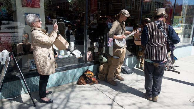 Jane Crisler, a tourist from France, takes a picture of a band playing on Haywood Street Tuesday March 29, 2016 in downtown Asheville.